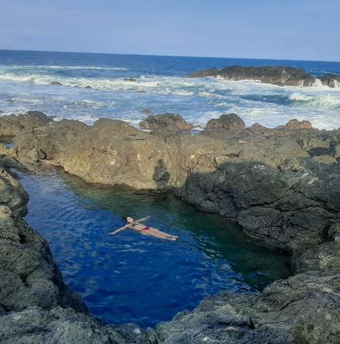 Woman floating in the tide pool at Amor De Mar, Montezuma Costa Rica