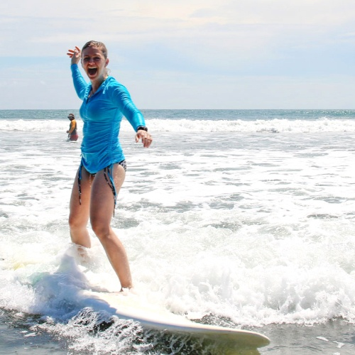 woman smiling catching a wave