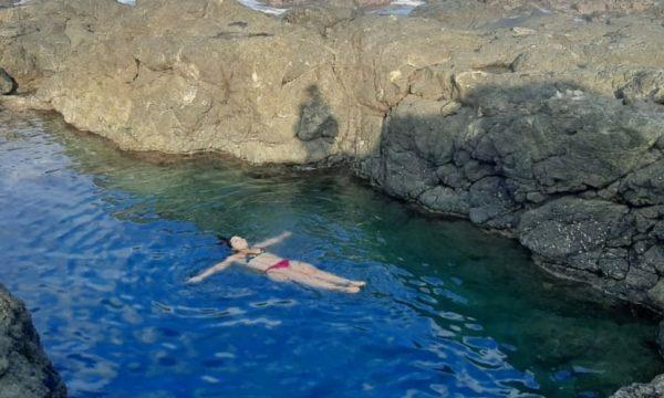 woman floating in the Amor De Mar Tide Pool